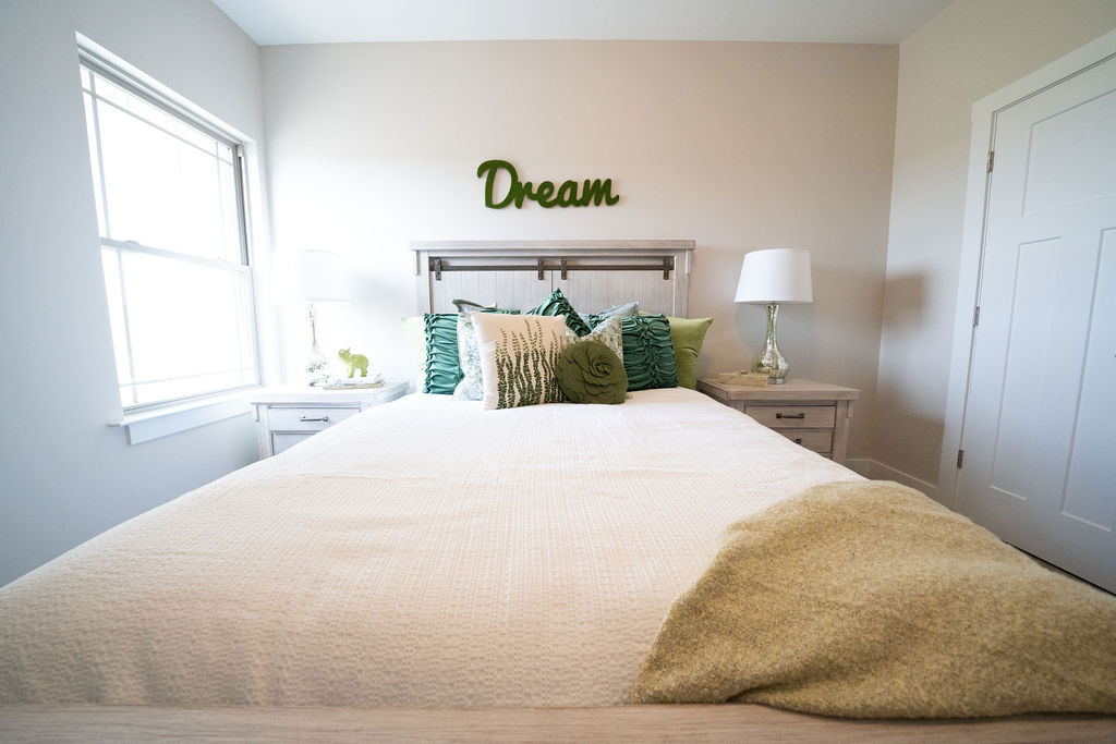 "Close-up of bed in master bedroom with overhead sign that says ""Dream"""