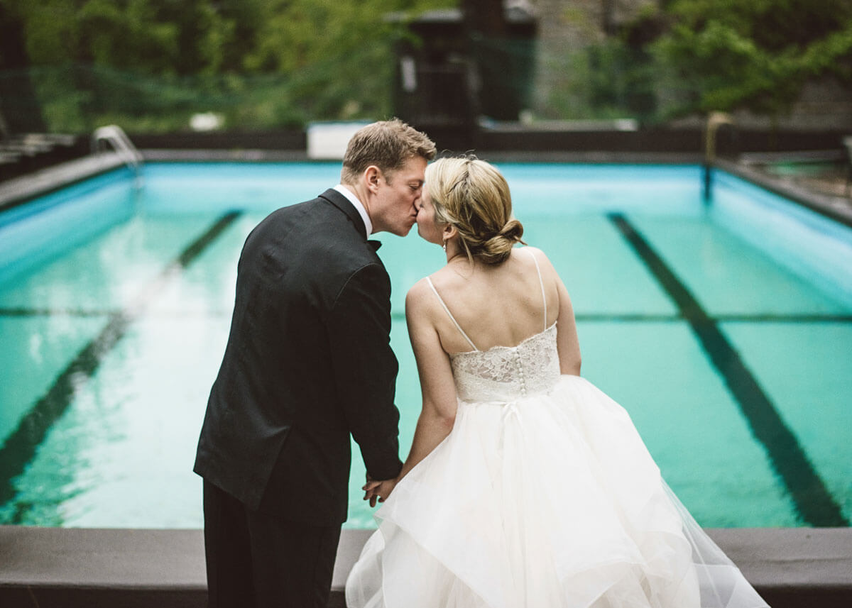 Bride and groom kissing by the swimming pool