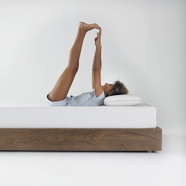 Women lying on back stretching to touch toes while on a Ergoflex mattress