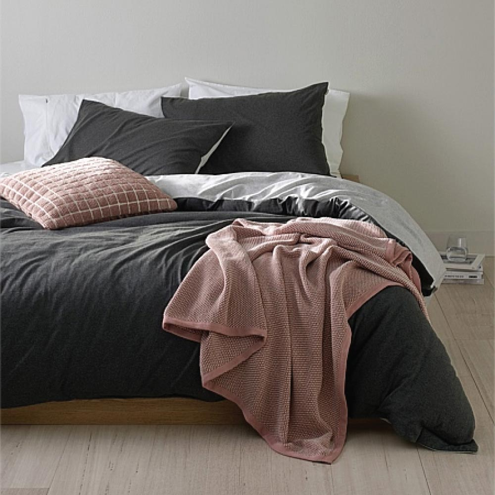 Pink Country Road throw draped over the end of a bed