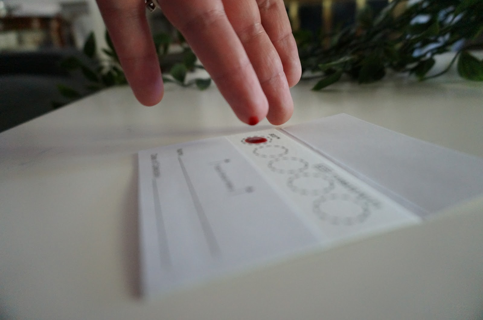 Blood droplet falling onto collection card for thyroid blood test sample