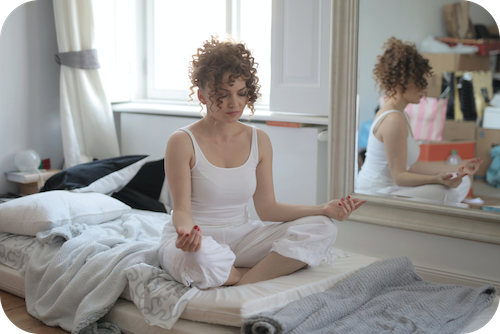 Woman practices meditation in bedroom as stress reduction