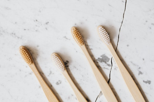 A photo of wood toothbrushes on a marble countertop to highlight the importance of proper dental hygiene for thyroid health