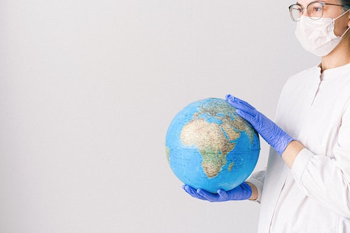 Image of women holding a globe in white lab coat, white face mask, and blue gloves representing the COVID-19 pandemic