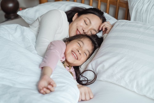 Image of mom and daughter laying down in bed, smiling, with white pillows and sheets