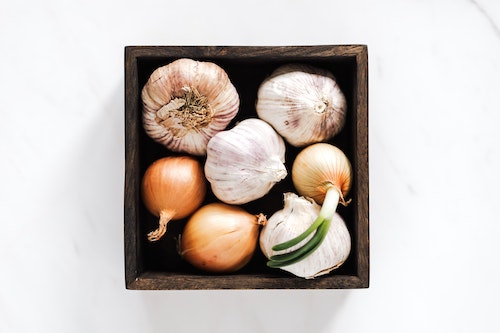 Onion and garlic in small, brown wooden box on white surface above text about odorous food causing body odor