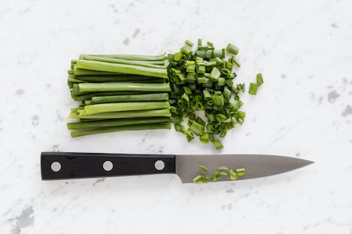 A bunch of partially-chopped green onions and a kitchen knife with black handle laid flat on a while marble counter