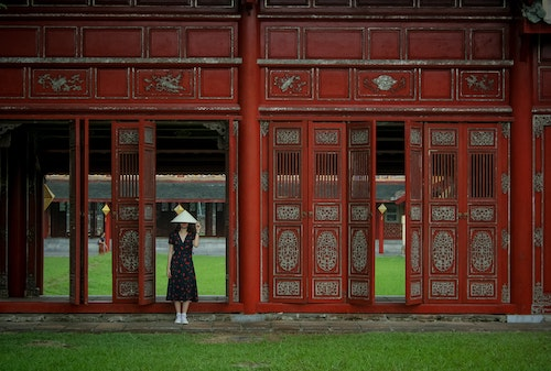 Woman in black dress standing in front of red doors in Thành phố Huế, Vietnam