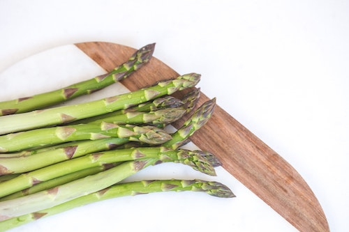 Asparagus stalks on marble and wood cutting board on white background