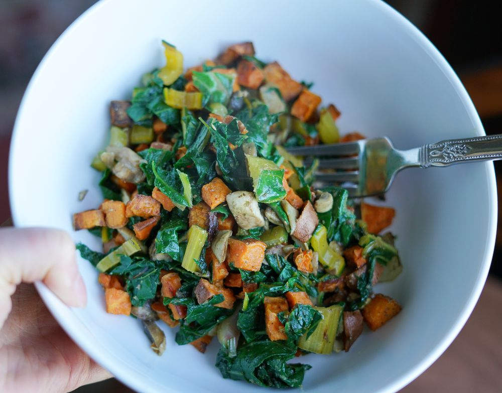 Rainbow chard with sweet potatoes and mushrooms in white ceramic bowl with stainless steel fork