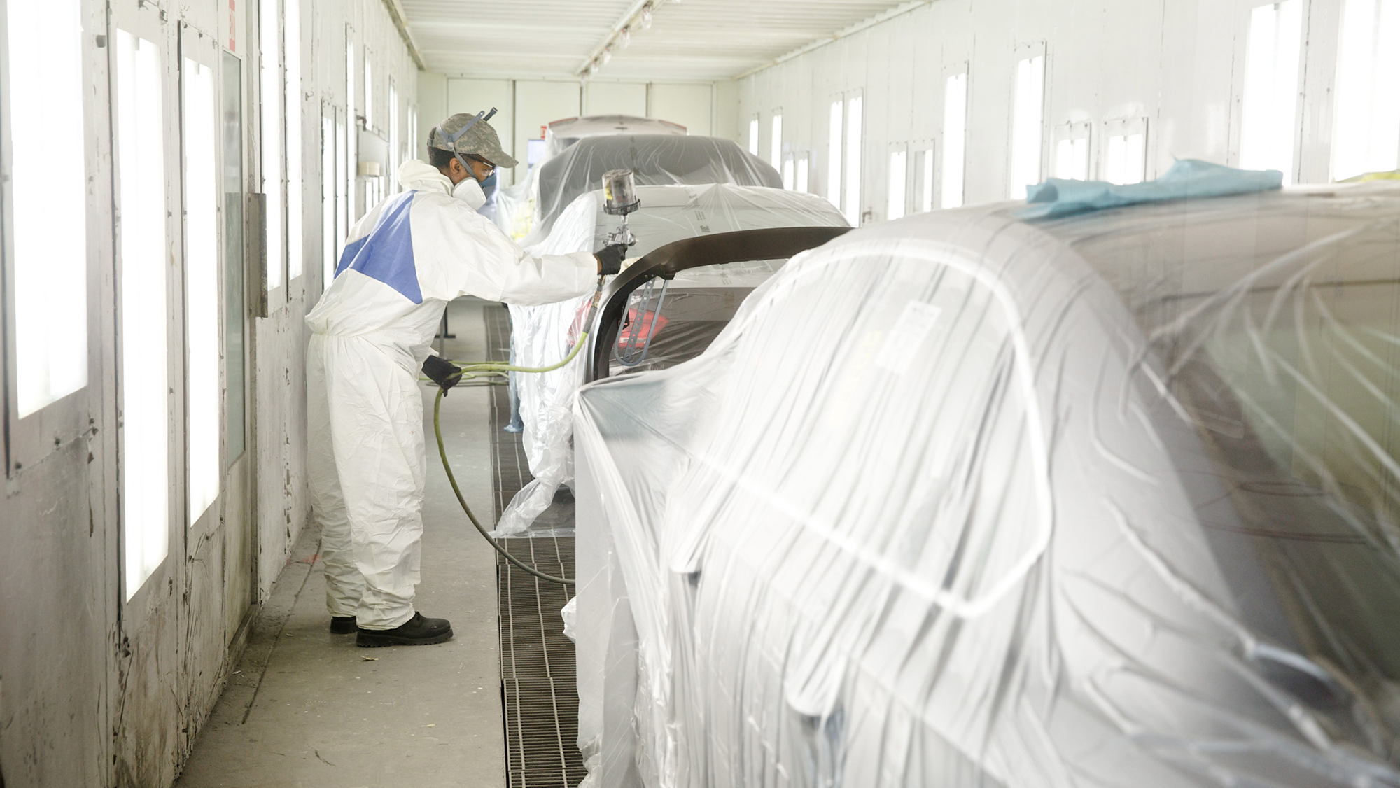 Worker painting car