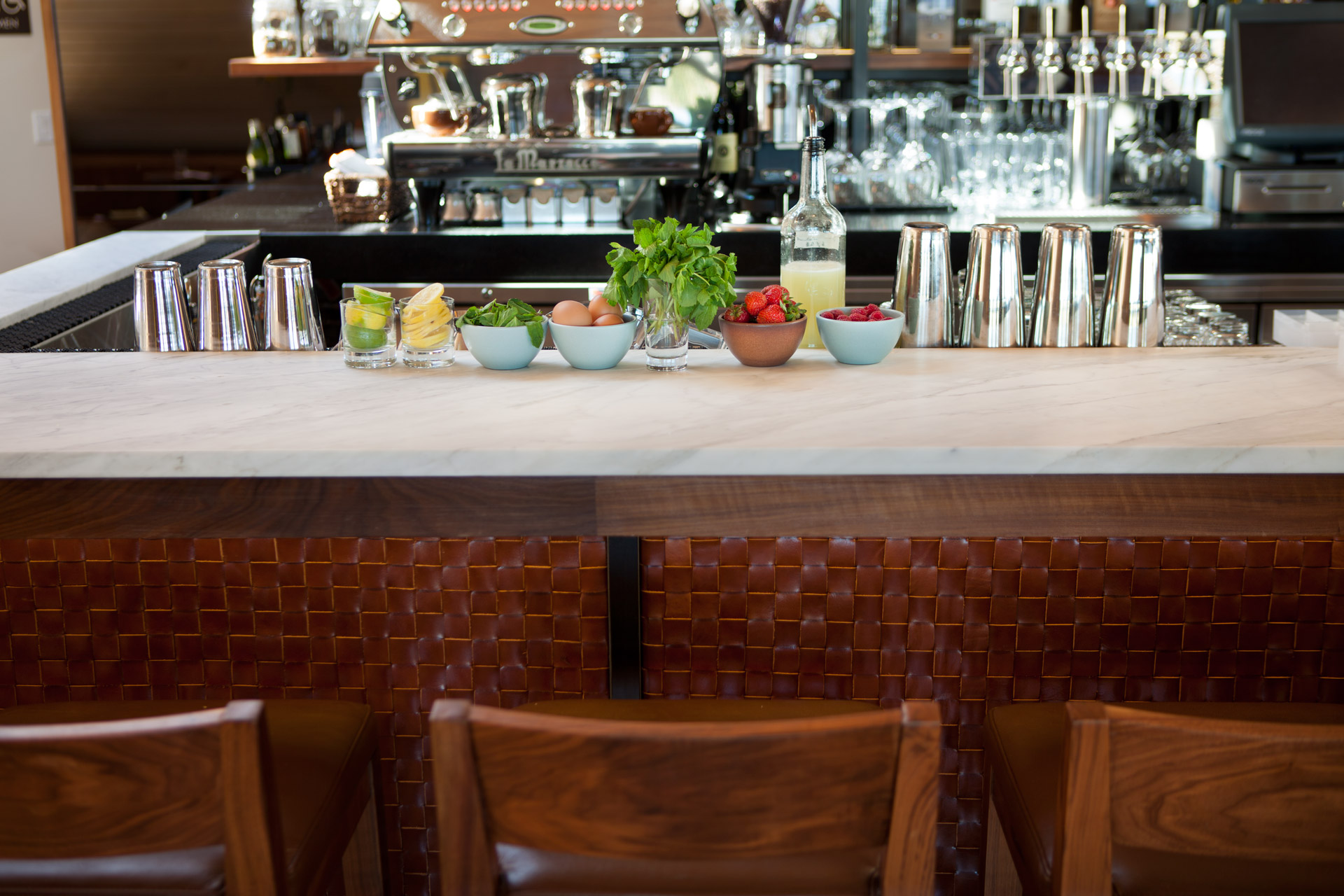 Close up of a bar with brown leather checkered pattern bar trim and white marble bar top. Three brown wooden barstools align the front. Lemon, strawberry, egg, mint garnishes in white bowls are on top of the bar. Several silver metal tumblers and mixology tools are at and behind the bar. Barrel House Tavern, Sausalito, California