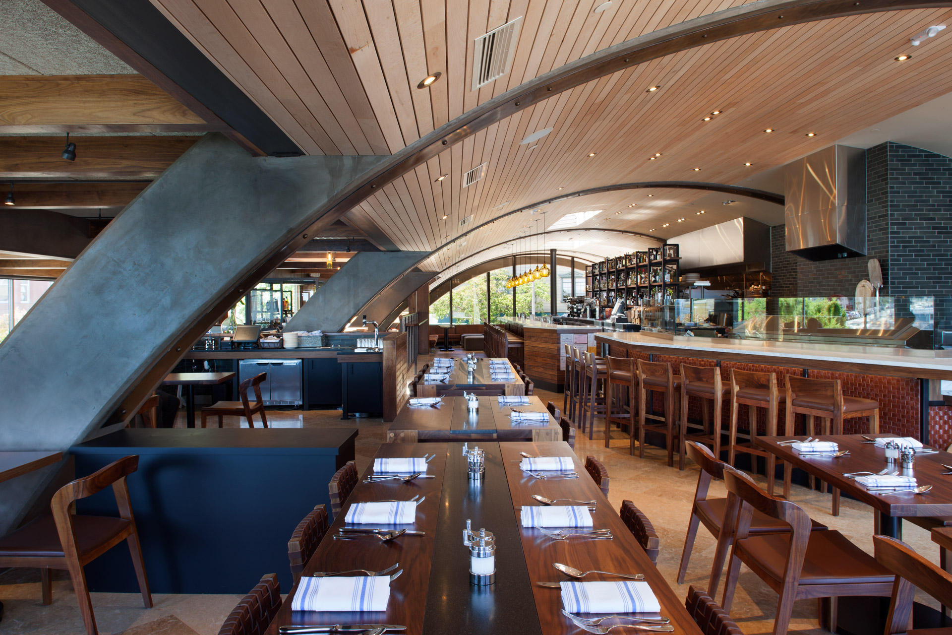 A restaurant with several dining brown wooden dining tables extended from the center, with white and light blue striped napkins and place settings. An open kitchen with glossy black tile is on the right, and further back is the bar with hanging yellow pendants. Curved concrete columns extend from the left over to the ceiling. The ceiling is curved and made of wooden brown slats, resembling a barrel. Barrel House Tavern, Sausalito, California
