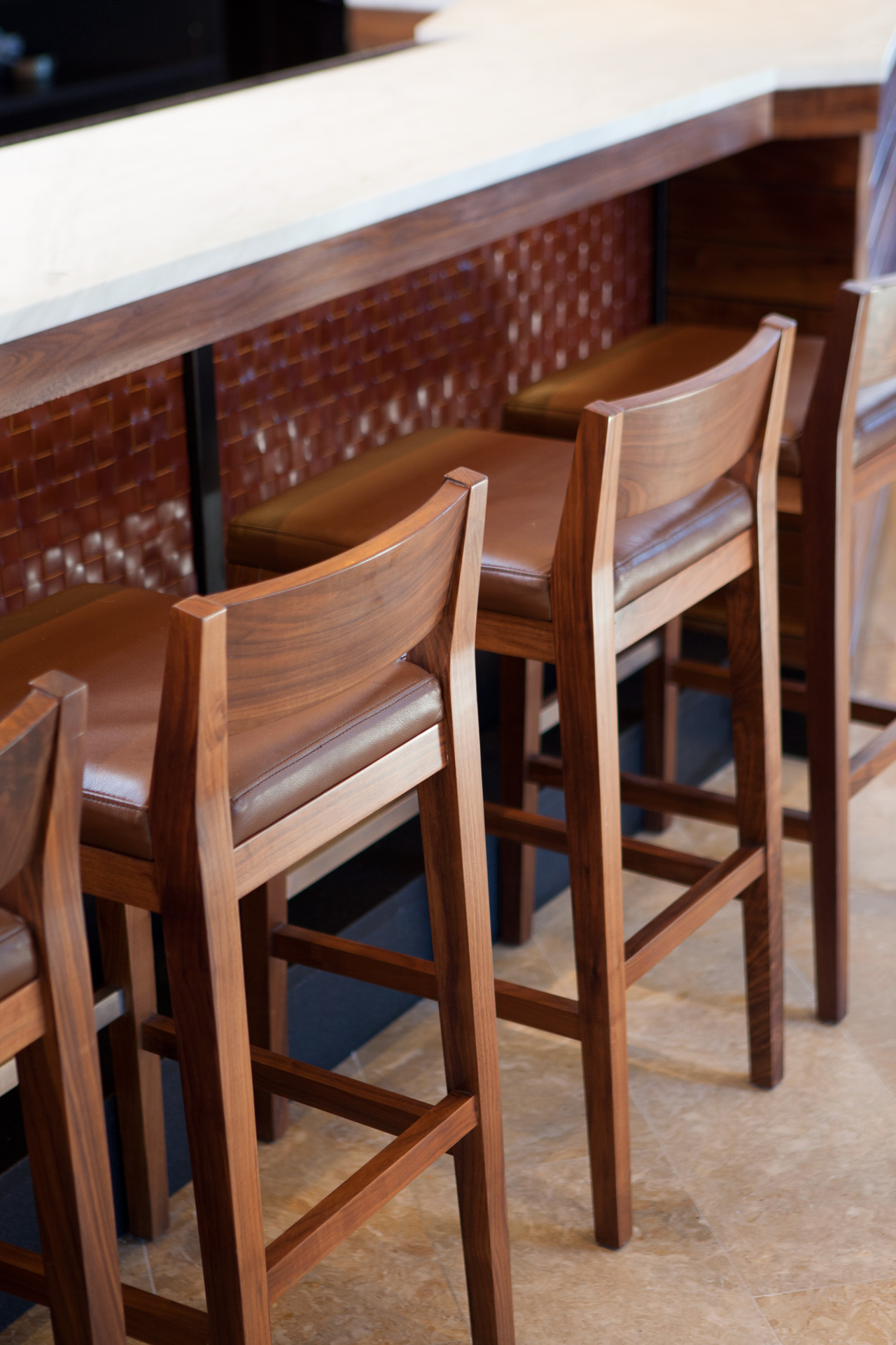 Close up of two brown wooden barstools with brown leather seats. The stools are at a brown wooden bar with white marble bar top. Barrel House Tavern, Sausalito, California