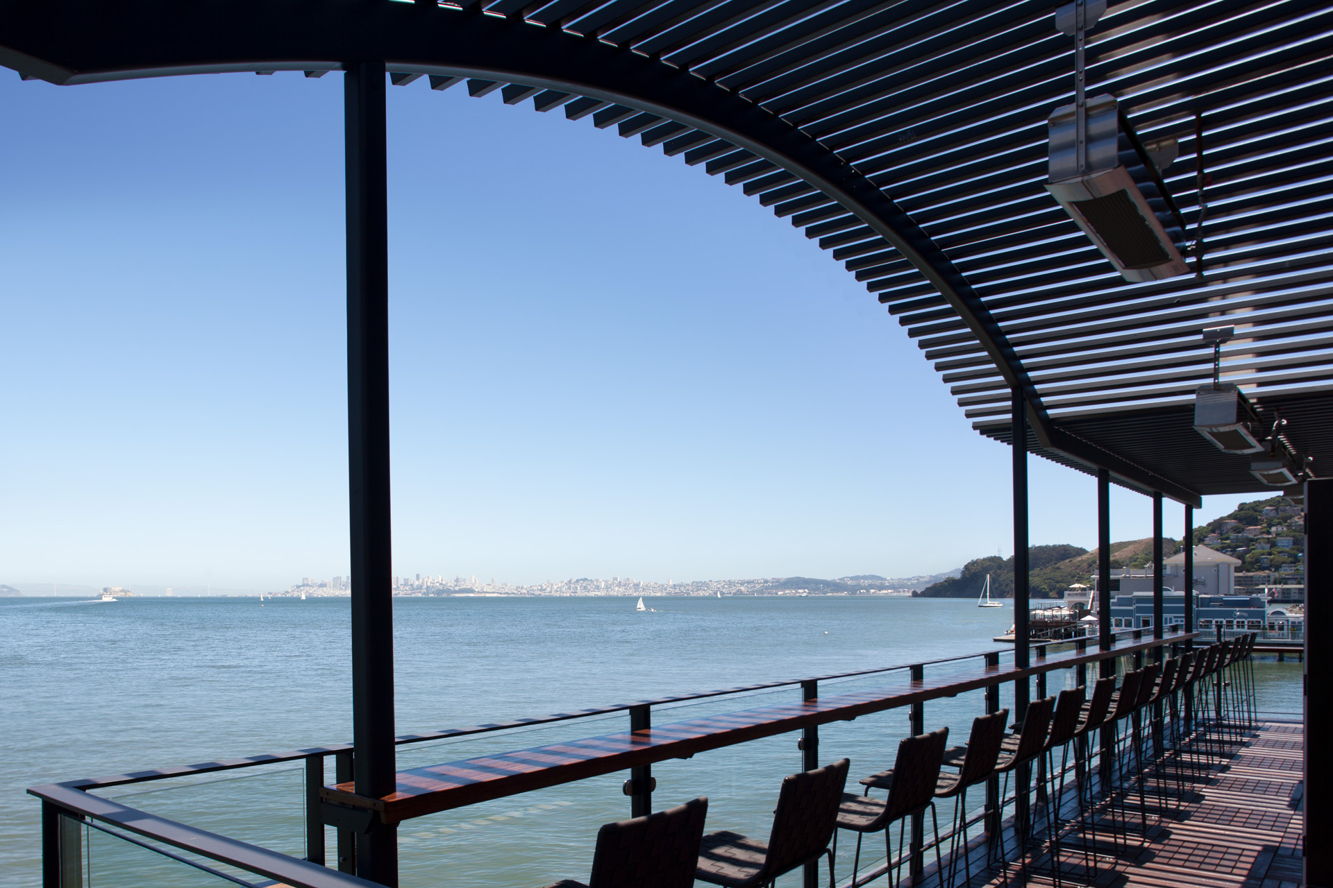 Outdoor dining area lined with black fabric barstools and overlooking the water at the San Francisco Bay. Barrel House Tavern, Sausalito, California