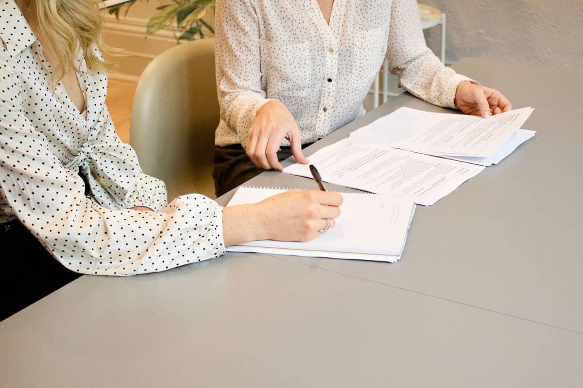 Zwei Frauen an einem Tisch unterschreiben einen Vertrag.