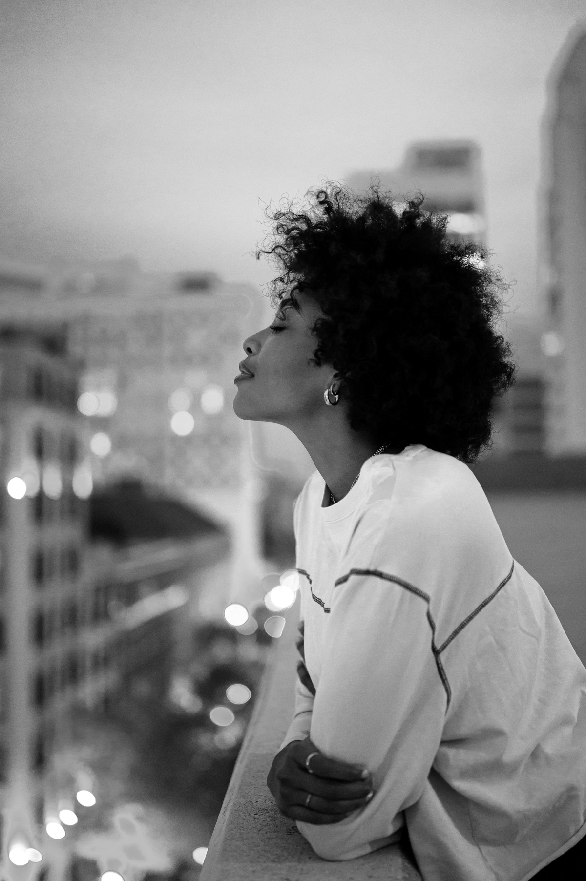 woman of color looking peacefully at the city lights