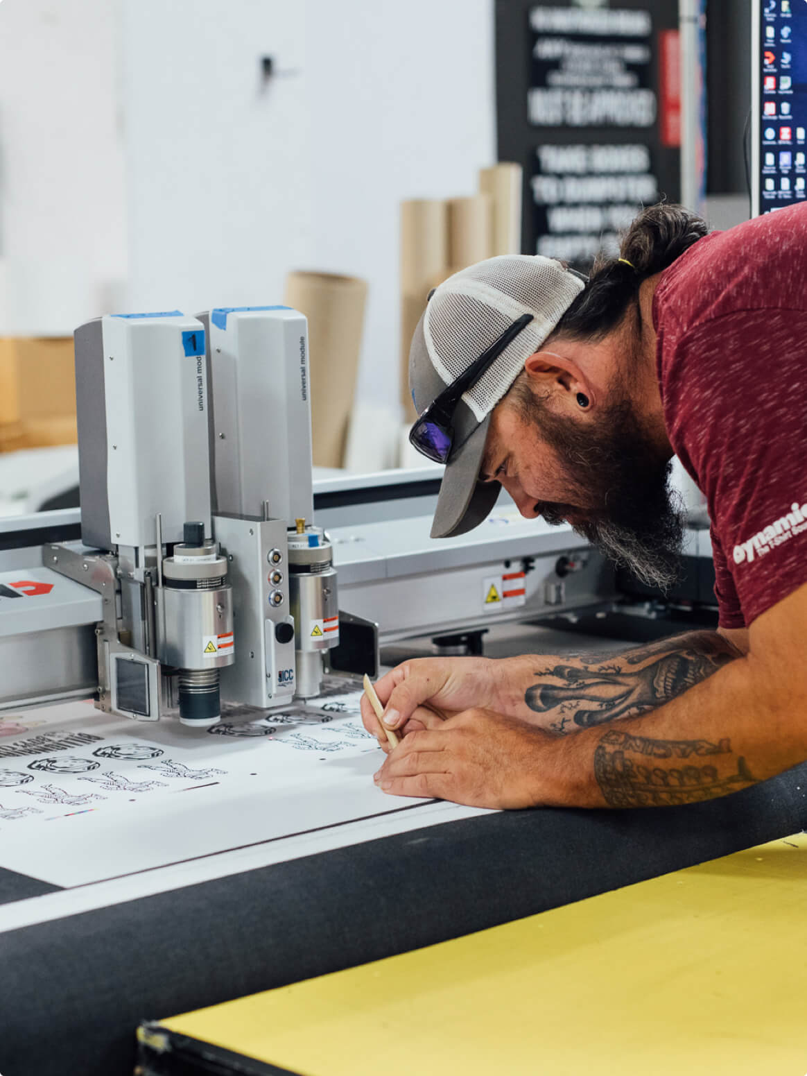 A Go Decals worker uses a pick to gently get die cut decals out of a printed sheet.