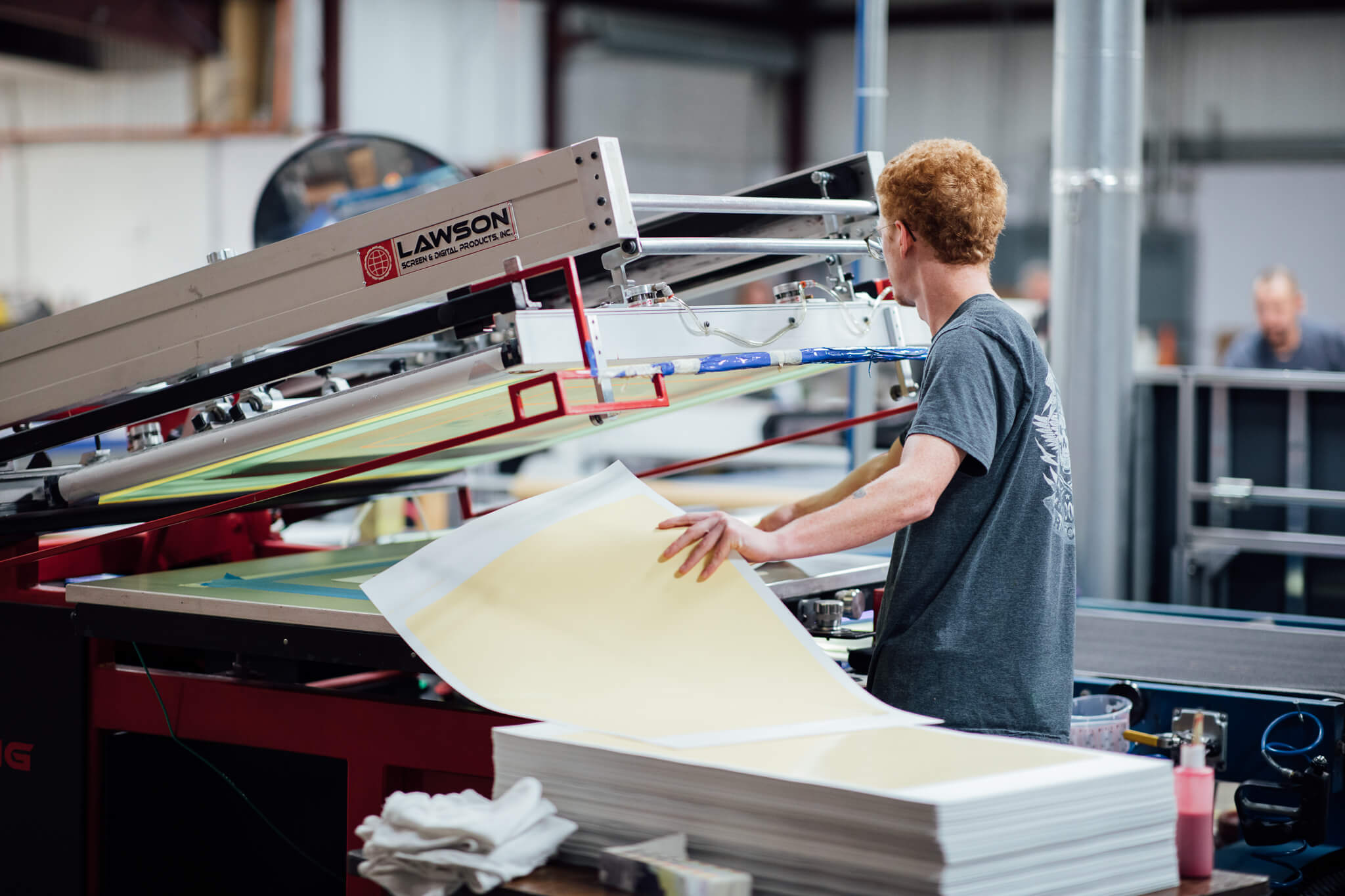 A GoD ecals worker places a vinyl sheet onto a screen printing machine.