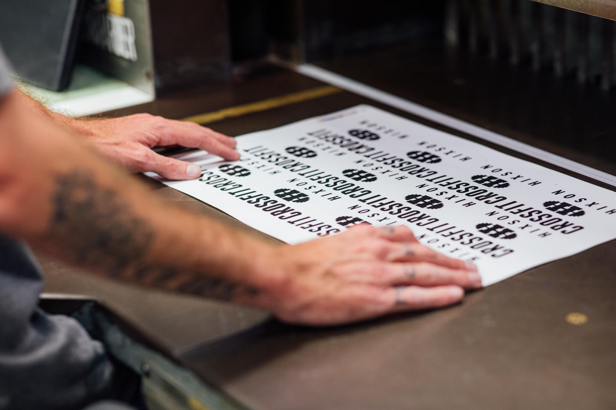 A sheet of decals for Hixson Crossfit gets cut by a guillotine