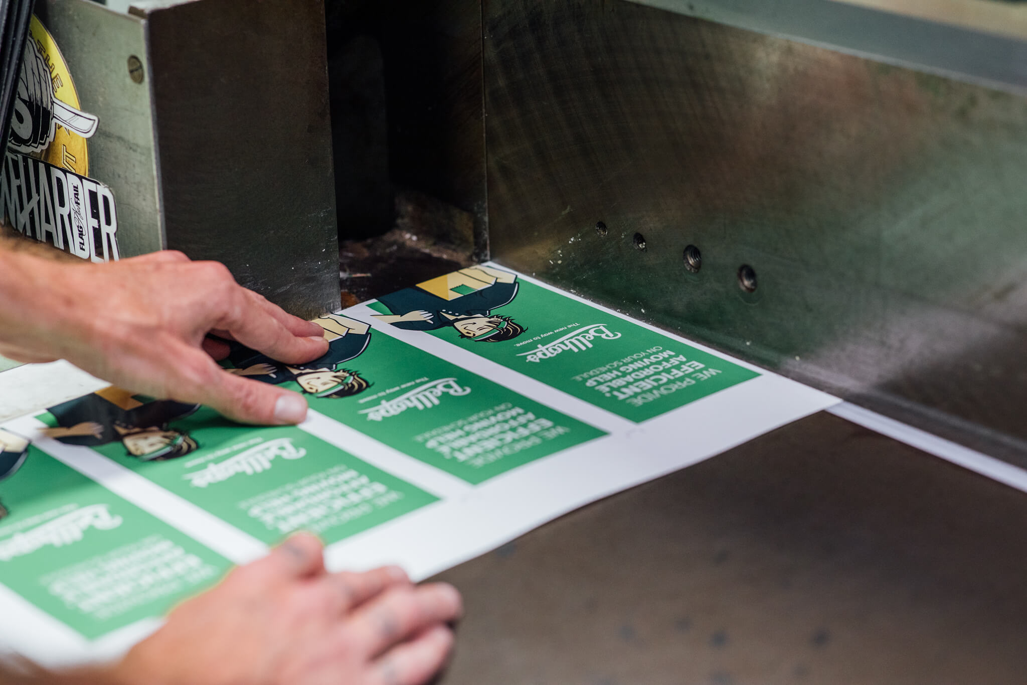 Bellhops vinyl decals getting cut by a guillotine