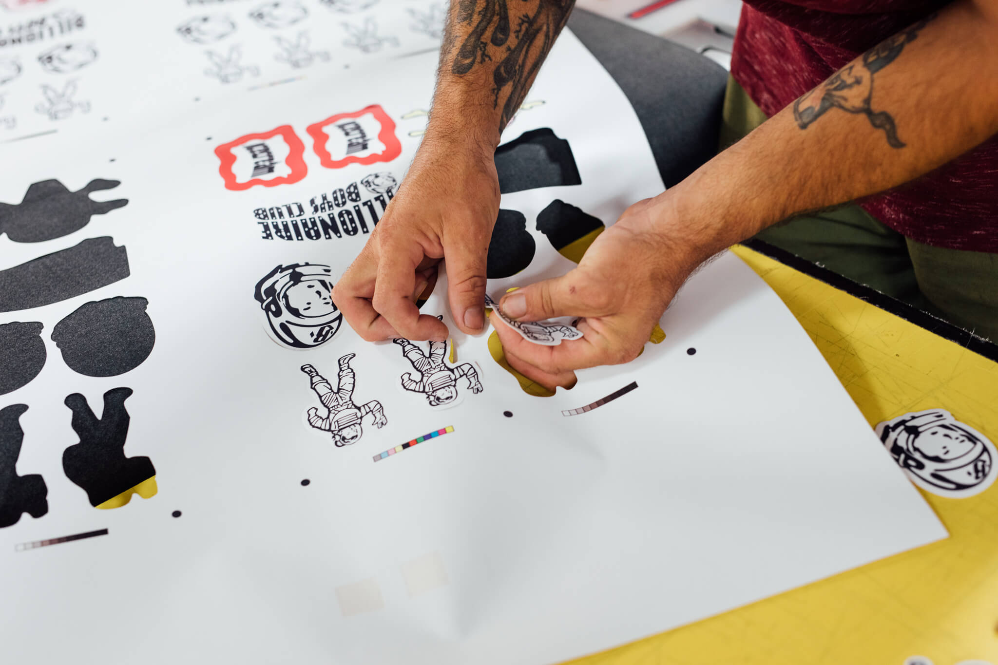 A Go Decals worker picks out die cut decals for Billionaire Boys Club from a printed sheet