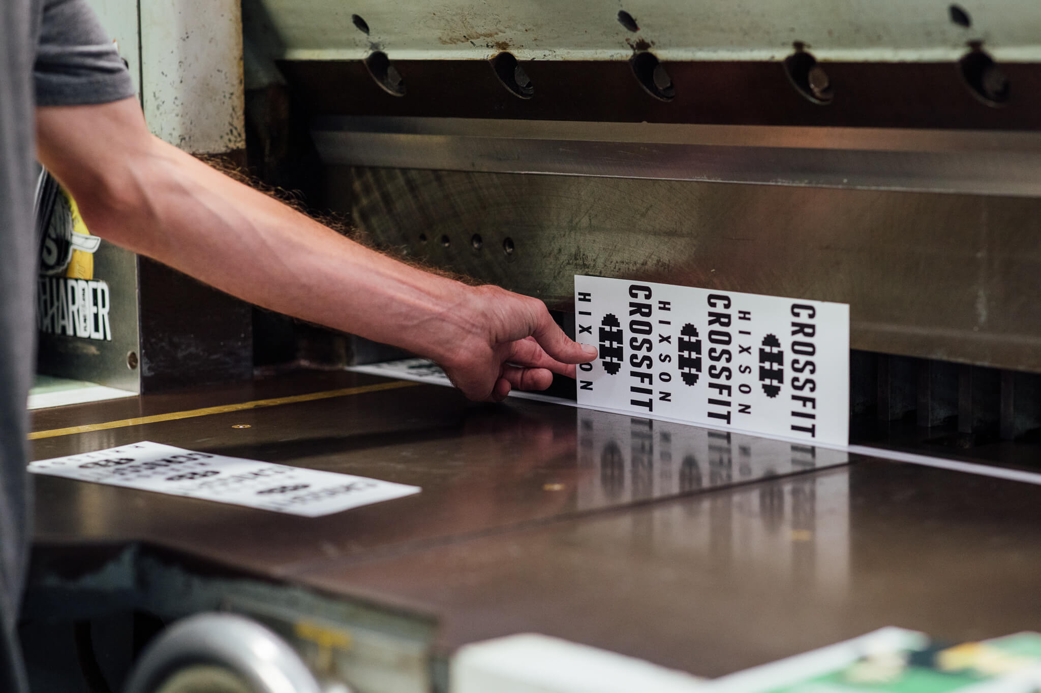 A Go Decals worker uses a Guillotine to cut Crossfit Hixson Stickers