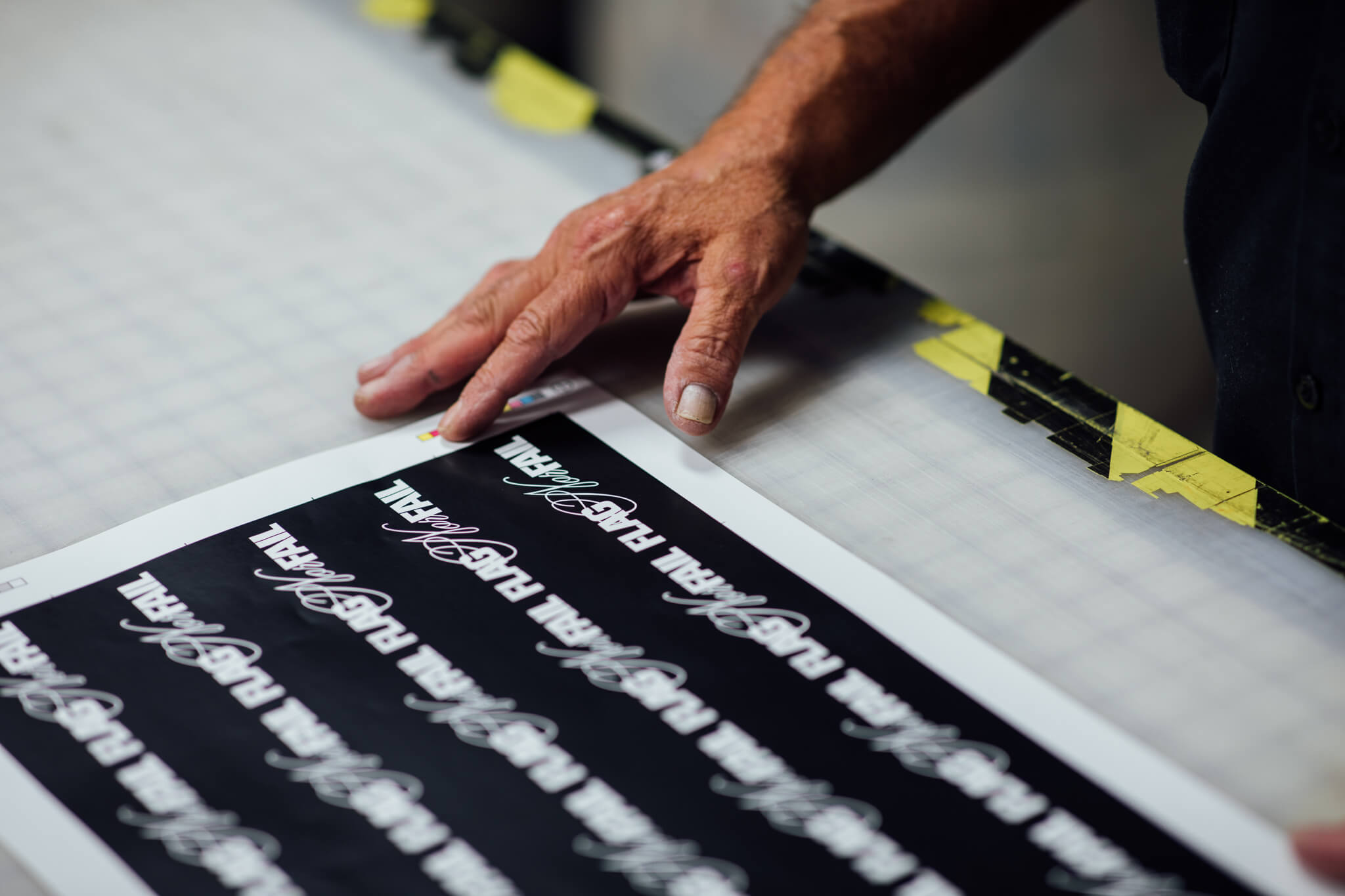 A Go Decals worker looks at a sheet of stickers placed on the table.