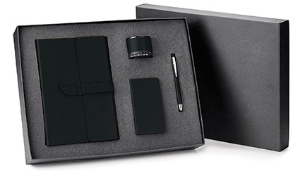 A box set with a portfolio, a pen, a power bank, and a bluetooth speaker, all in black.