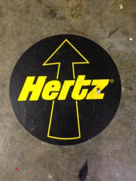 A floor graphic printer for Hertz with an arrow pointing ahead.
