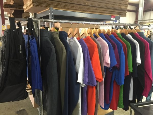 An rack of branded shirts, coats, and jackets.