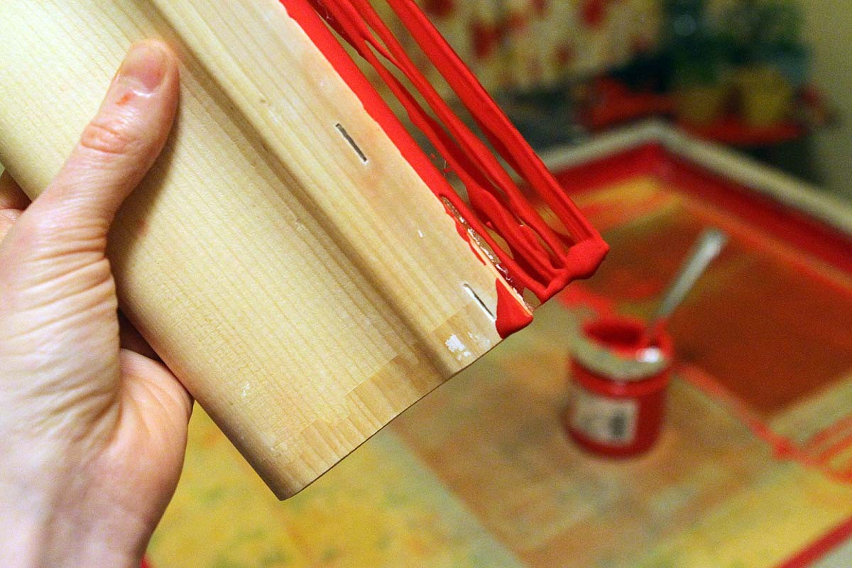 A screen printing squeegee dripping with ink
