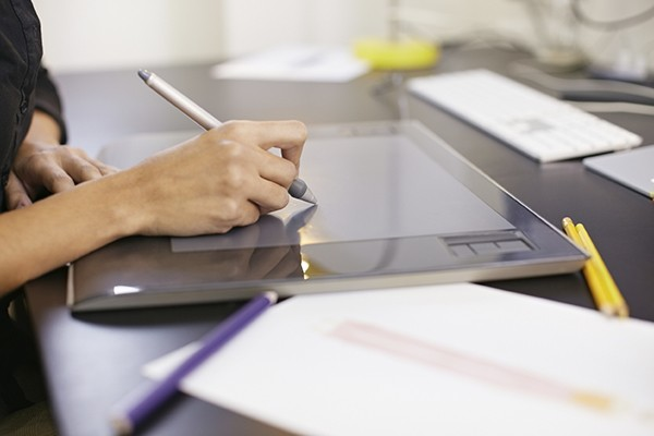 A designer uses a stylus on a drawing tablet.