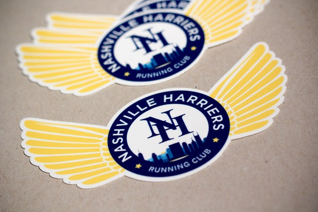 A die cut sticker for Nashville Harriers Running Club with die cut revealing extended wings coming out of a central seal.