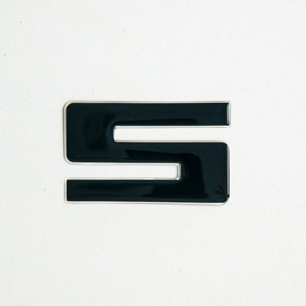 "Product shot of a letter ""S"" Domed Decal. The black decal is glossy and refelctive."