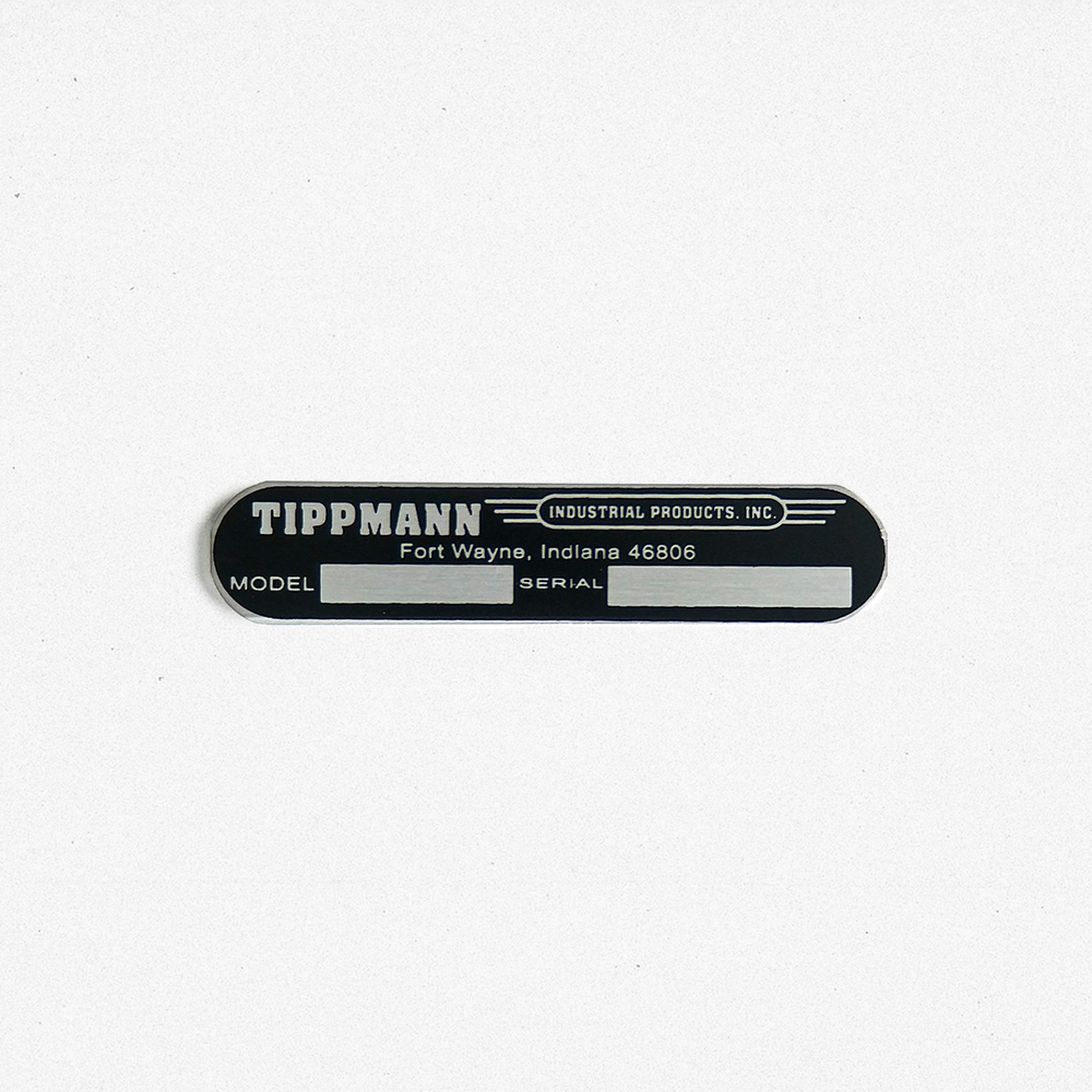 A product photo of a custom metal nameplate for Tippmann.