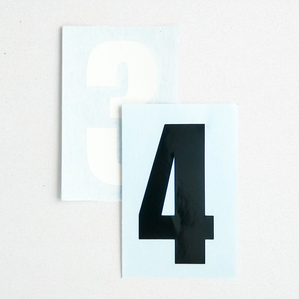 Product shot of two vinyl number stickers. One is white and one is black.