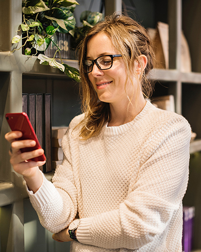 Young woman with glasses indoors using the Phlo app on her mobile device