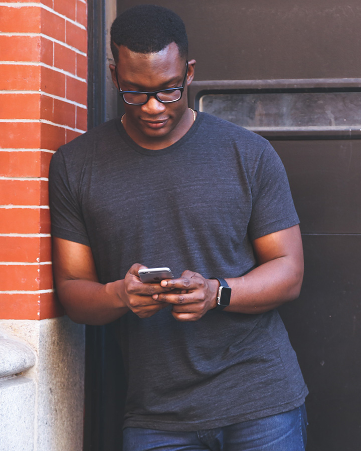 image of young man with glasses outside using his mobile phone