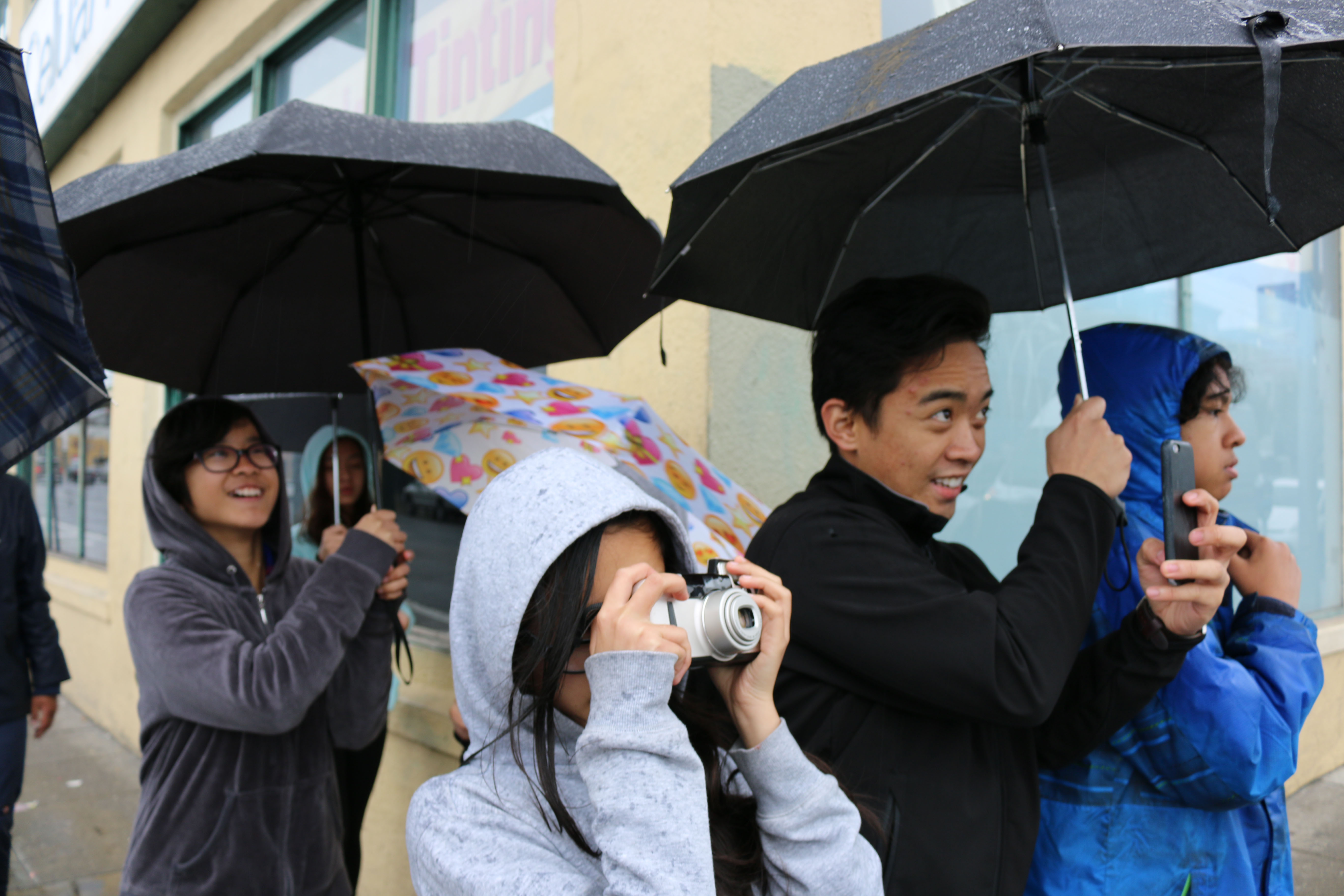 Yung scholarz with co-educator taking film photos in the rain in SOMA Pilipinas, SoMapagmahal, 2017.