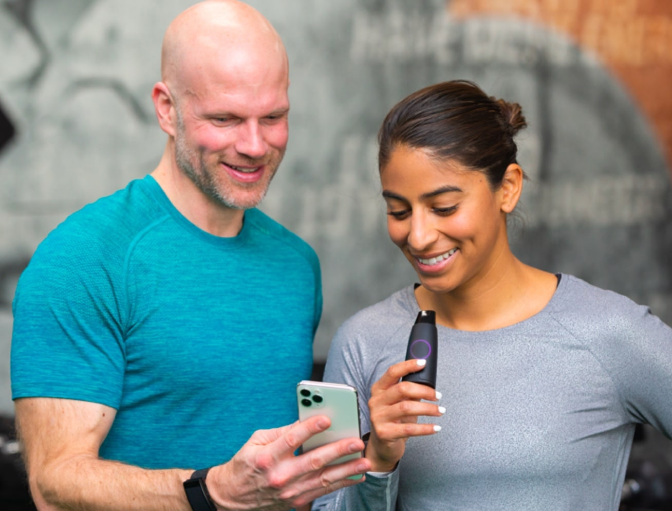 Man and a woman looking at a phone while using a Lumen device.