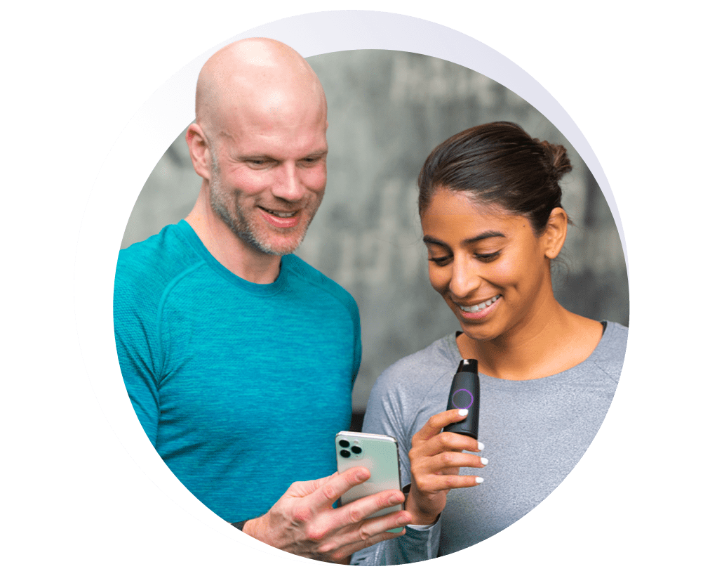 A man and a woman holding a Lumen device while looking at a phone.