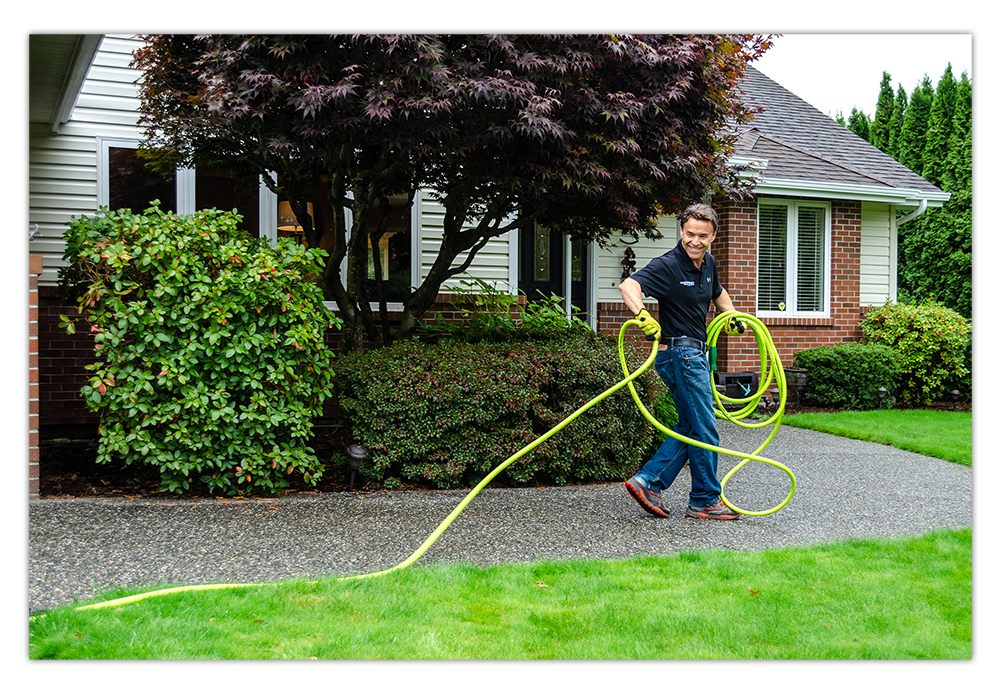 Man carrying a hose outside