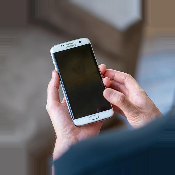 En TechBuddy håller i en smartphone