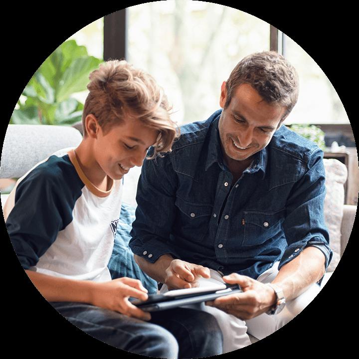 En pappa och son sitter med en iPad.