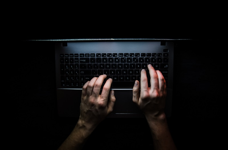 Ett tagentbord på en laptop i ett mörkt rum.
