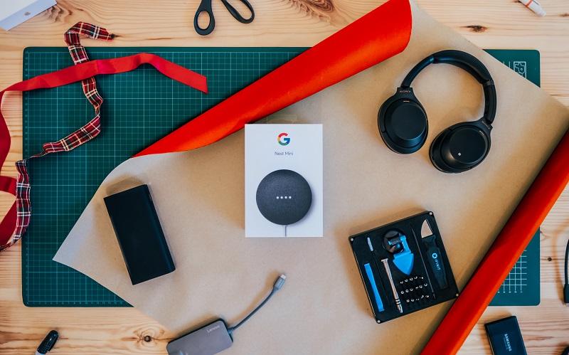 Stor bild med bord med presentpapper, Google Home Mini och hörlurar.
