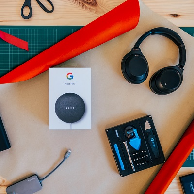 Liten bild med bord med presentpapper, Google Home Mini och hörlurar.
