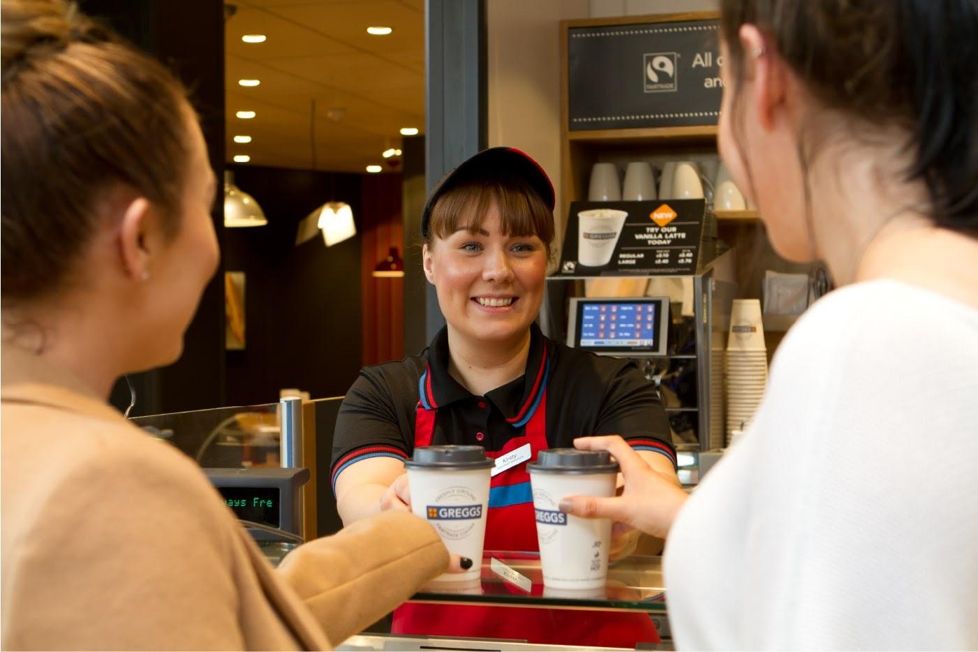 Greggs employee handing over coffees