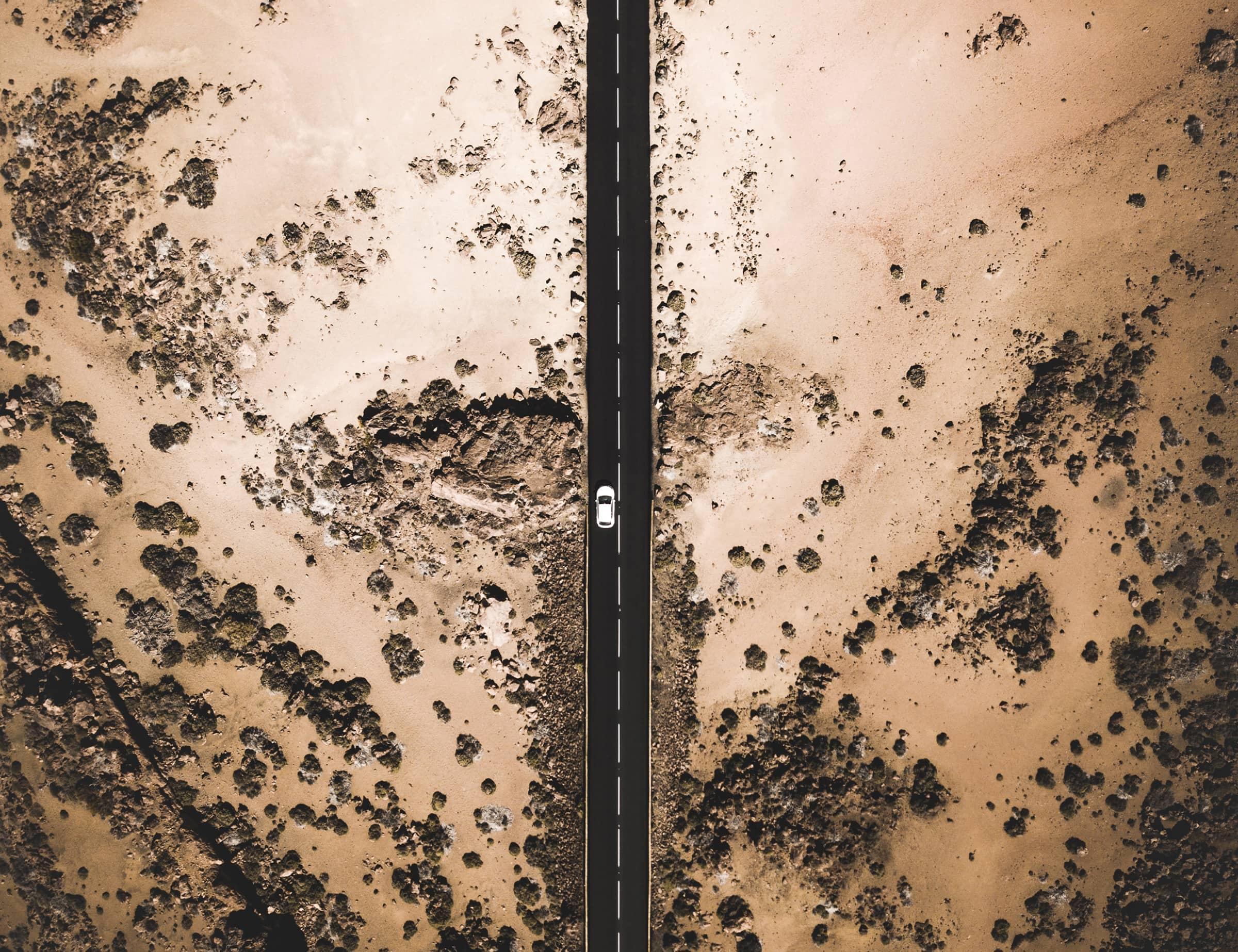 an arial shot of a car driving down a desert road